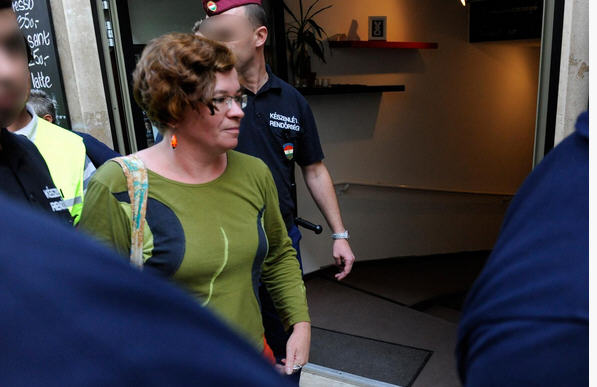 Veronika Móra, director of the Ökorárs Foundation, is being escorted by policemen to police headquarters